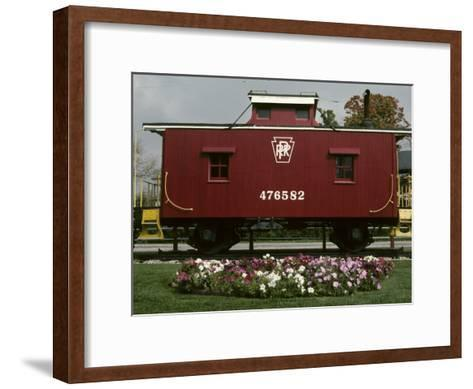 A Bright Red Caboose and a Flower Bed Compete for Vivid Color-Stephen St^ John-Framed Art Print