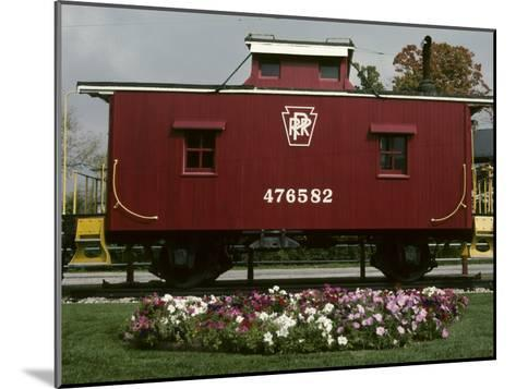 A Bright Red Caboose and a Flower Bed Compete for Vivid Color-Stephen St^ John-Mounted Photographic Print