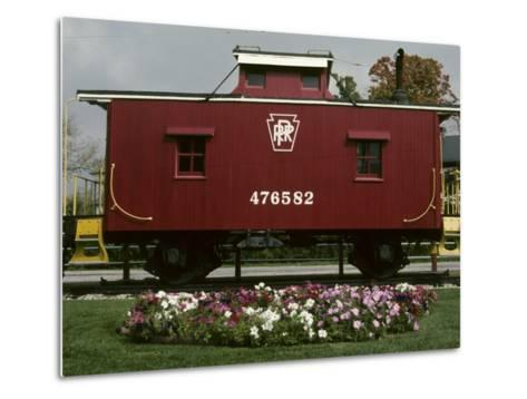 A Bright Red Caboose and a Flower Bed Compete for Vivid Color-Stephen St^ John-Metal Print
