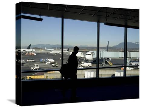 A Silhouette Walks Past a Window Looking Out at the Tarmac, Vancouver, British Columbia, Canada-Taylor S^ Kennedy-Stretched Canvas Print