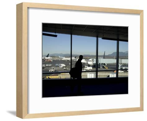 A Silhouette Walks Past a Window Looking Out at the Tarmac, Vancouver, British Columbia, Canada-Taylor S^ Kennedy-Framed Art Print