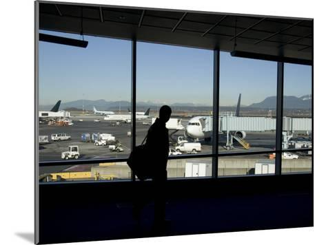 A Silhouette Walks Past a Window Looking Out at the Tarmac, Vancouver, British Columbia, Canada-Taylor S^ Kennedy-Mounted Photographic Print