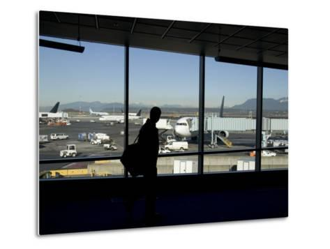 A Silhouette Walks Past a Window Looking Out at the Tarmac, Vancouver, British Columbia, Canada-Taylor S^ Kennedy-Metal Print