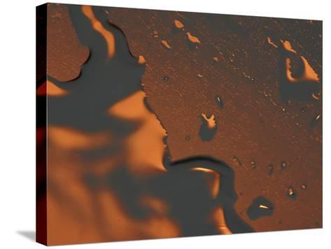 Close-up of Illuminated Orange Water Droplets and a Puddle on a Shiny Surface--Stretched Canvas Print