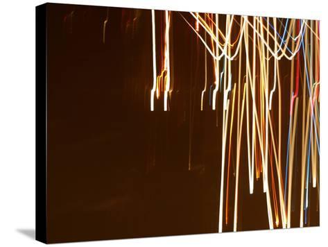 Colorful Streaks and Swirls of Light Against a Black Background--Stretched Canvas Print