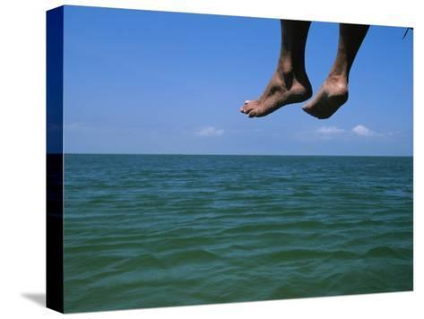 Sandy Feet Dangle Off the Side of a Dock on Portsmouth Island-Stephen Alvarez-Stretched Canvas Print