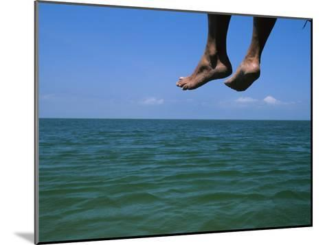Sandy Feet Dangle Off the Side of a Dock on Portsmouth Island-Stephen Alvarez-Mounted Photographic Print