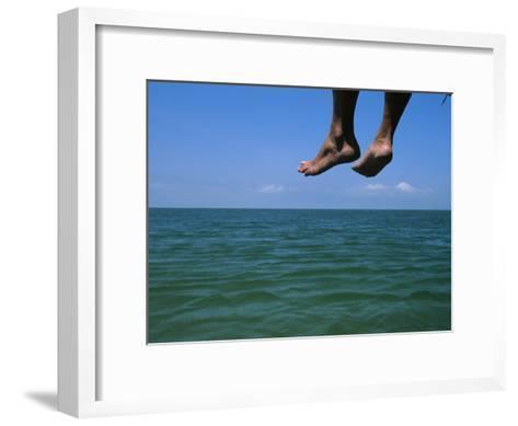 Sandy Feet Dangle Off the Side of a Dock on Portsmouth Island-Stephen Alvarez-Framed Art Print