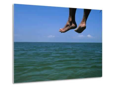 Sandy Feet Dangle Off the Side of a Dock on Portsmouth Island-Stephen Alvarez-Metal Print