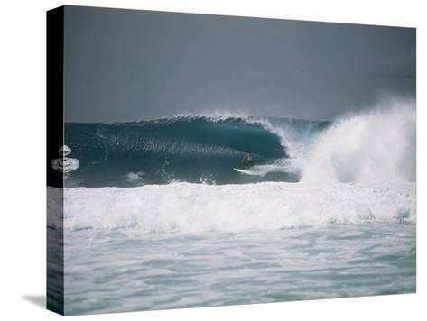 Surfer Riding a Wave in the Bonsai Pipeline in Oahu-Todd Gipstein-Stretched Canvas Print