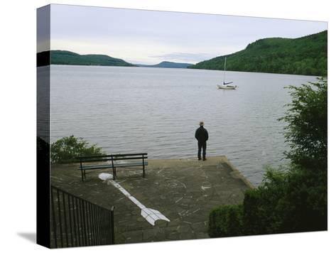 A Man Looks out at a Sailboat Anchored on Otsego Lake-Raymond Gehman-Stretched Canvas Print