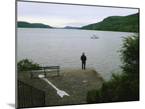 A Man Looks out at a Sailboat Anchored on Otsego Lake-Raymond Gehman-Mounted Photographic Print