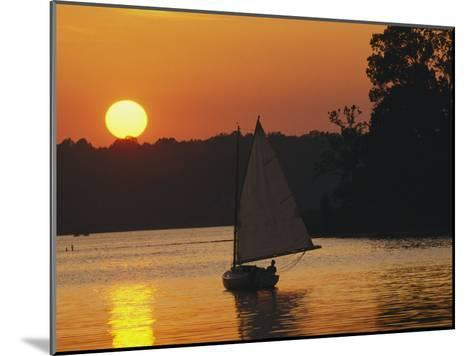 Gaff-Rigged Catboat Sails Along the Shoreline at Sunset-Skip Brown-Mounted Photographic Print