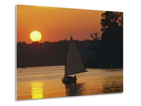 Gaff-Rigged Catboat Sails Along the Shoreline at Sunset-Skip Brown-Metal Print