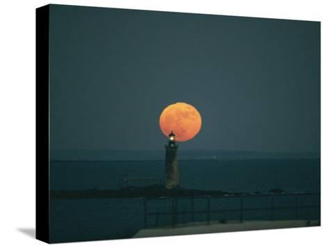 A Lighthouses Silhouette against a Full Moon-Bill Curtsinger-Stretched Canvas Print