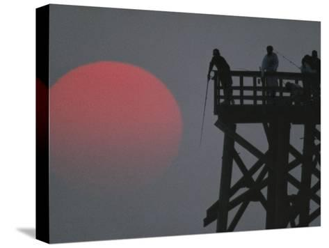 A Harvest Moon Rises over a Pier Where a Group of Fishermen Cast Their Lines-Joel Sartore-Stretched Canvas Print
