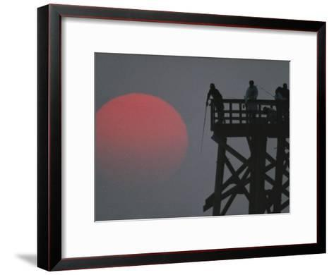 A Harvest Moon Rises over a Pier Where a Group of Fishermen Cast Their Lines-Joel Sartore-Framed Art Print