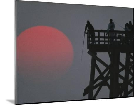 A Harvest Moon Rises over a Pier Where a Group of Fishermen Cast Their Lines-Joel Sartore-Mounted Photographic Print