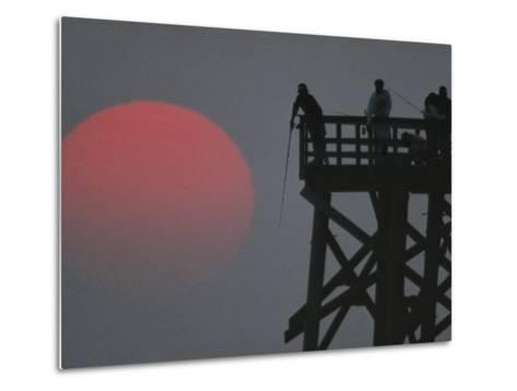 A Harvest Moon Rises over a Pier Where a Group of Fishermen Cast Their Lines-Joel Sartore-Metal Print