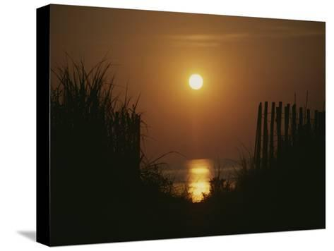 Sunrise over the Ocean Silhouettes Dunes and Erosion Fences-Stephen St^ John-Stretched Canvas Print