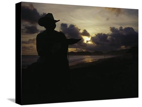 A Cowboy on His Horse Enjoys Sunrise on a Beach-Raul Touzon-Stretched Canvas Print