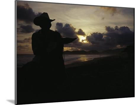 A Cowboy on His Horse Enjoys Sunrise on a Beach-Raul Touzon-Mounted Photographic Print