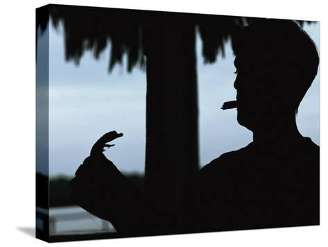 A Cigar-Smoking Cuban Man in Silhouette Holds a Baby Crocodile-Steve Winter-Stretched Canvas Print