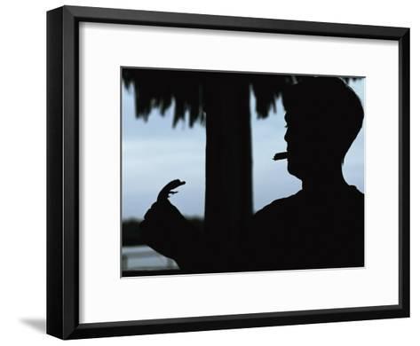 A Cigar-Smoking Cuban Man in Silhouette Holds a Baby Crocodile-Steve Winter-Framed Art Print