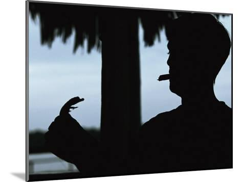 A Cigar-Smoking Cuban Man in Silhouette Holds a Baby Crocodile-Steve Winter-Mounted Photographic Print
