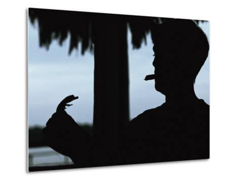 A Cigar-Smoking Cuban Man in Silhouette Holds a Baby Crocodile-Steve Winter-Metal Print