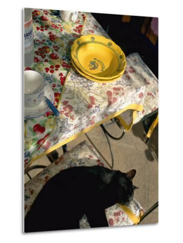 A Cat Lies on a Chair by a Table That is Set for a Meal-Tino Soriano-Metal Print