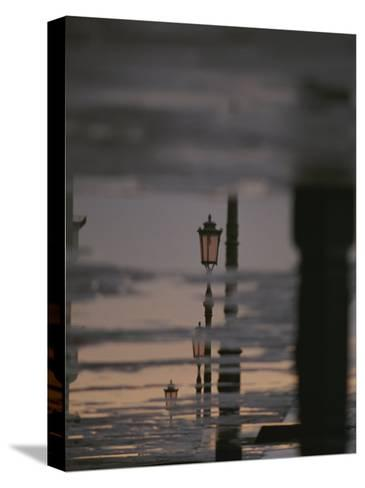 Lampposts Reflected on Wet Pavement after a Rain-Raul Touzon-Stretched Canvas Print