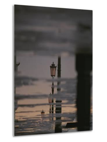 Lampposts Reflected on Wet Pavement after a Rain-Raul Touzon-Metal Print
