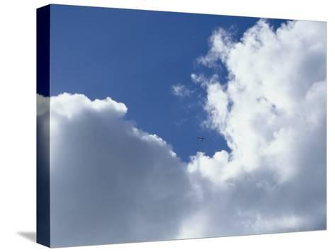 Distant Airplane in a Cloud-Filled Sky-Bill Curtsinger-Stretched Canvas Print