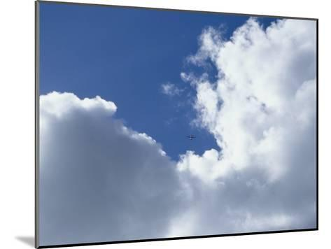Distant Airplane in a Cloud-Filled Sky-Bill Curtsinger-Mounted Photographic Print