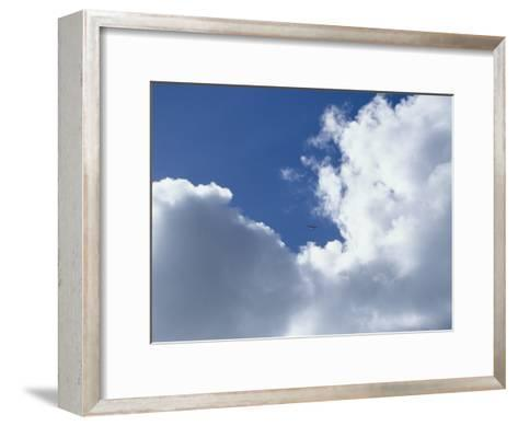 Distant Airplane in a Cloud-Filled Sky-Bill Curtsinger-Framed Art Print