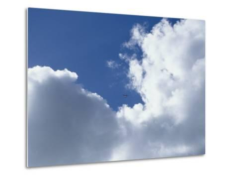Distant Airplane in a Cloud-Filled Sky-Bill Curtsinger-Metal Print