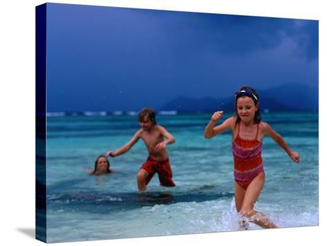 Children Running Out of Ocean in Stormy Weather, Seychelles-Philip & Karen Smith-Stretched Canvas Print