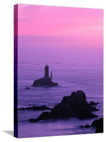 Silhouette of Lighthouse Against Pink Sky at Sunset, Pointe Du Raz, Brittany, France-Olivier Cirendini-Stretched Canvas Print