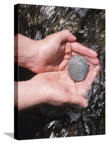 Person Holding Rock with the Word Blessings in Rushing Water--Stretched Canvas Print