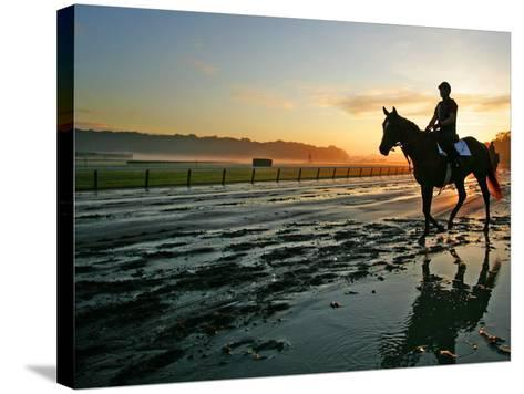 An Unidentified Horse and Rider on the Track at Sunrise at Belmont Park--Stretched Canvas Print