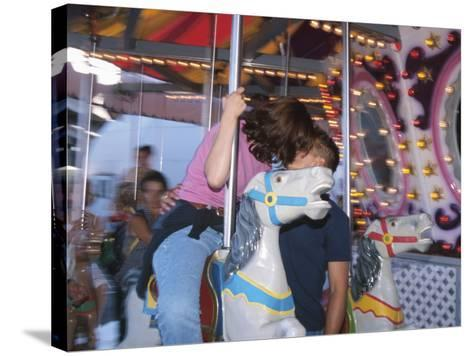 Young Couple Kissing on Carousel--Stretched Canvas Print