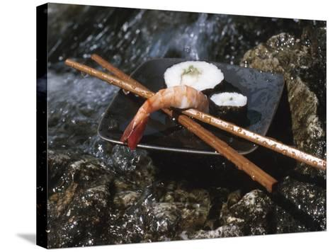 Elegant Sushi and Chopsticks Beside Rushing Water--Stretched Canvas Print