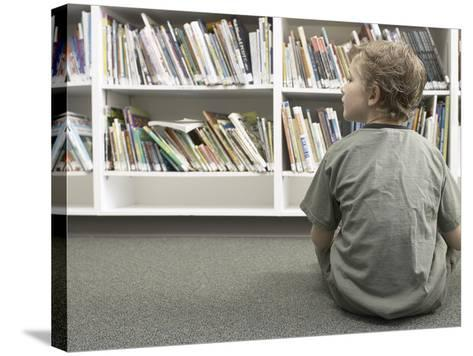 Little Boy Looking Rows of Books on Library Shelves--Stretched Canvas Print