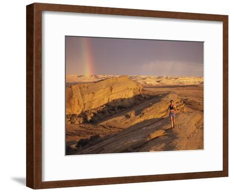 Woman Trail Running in a Rocky Landscape with a Rainbow-Bobby Model-Framed Art Print