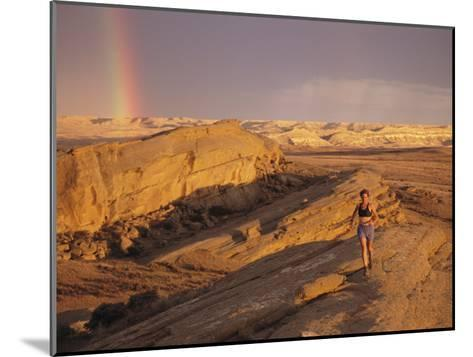 Woman Trail Running in a Rocky Landscape with a Rainbow-Bobby Model-Mounted Photographic Print