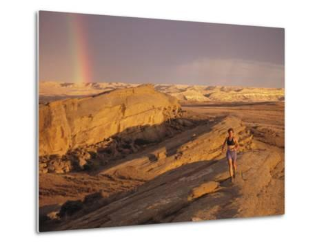Woman Trail Running in a Rocky Landscape with a Rainbow-Bobby Model-Metal Print