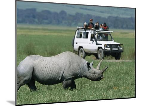 Tourists View a Rhinoceros from a Safari Jeep-Richard Nowitz-Mounted Photographic Print