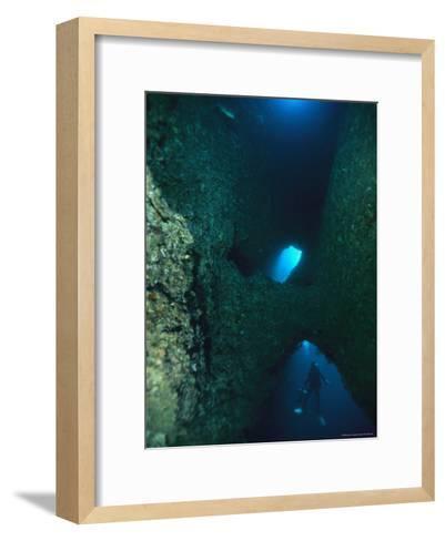 Diver Swimming Around Crevasses in a Reef Wall-Tim Laman-Framed Art Print