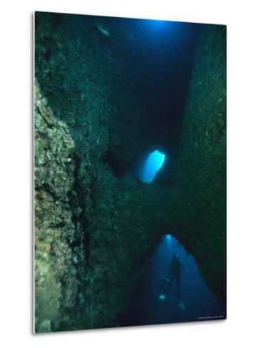 Diver Swimming Around Crevasses in a Reef Wall-Tim Laman-Metal Print